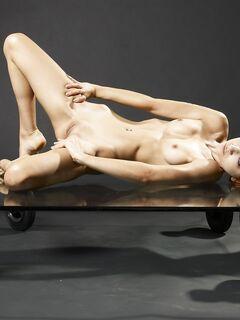 Тощая девица выгибается на стеклянном столе - фото