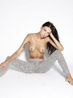 Красивая девушка топлес снимает лосины лежа на полу - фото