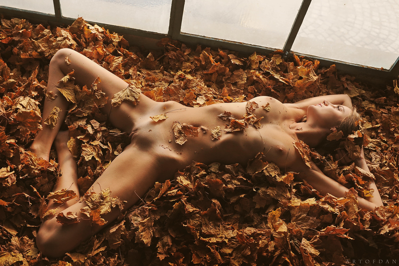 Голая девушка в осенней листве - фото
