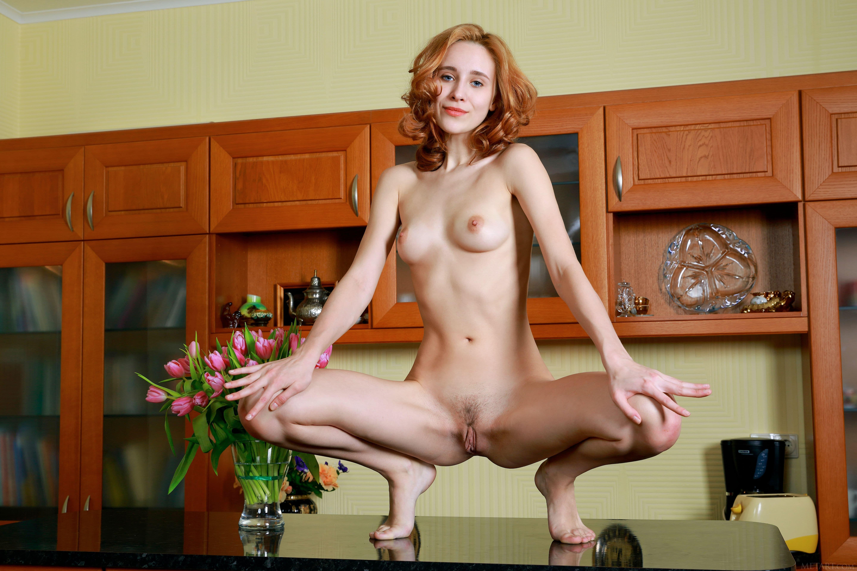 Рыжая девушка раздвинула ноги на столе - фото