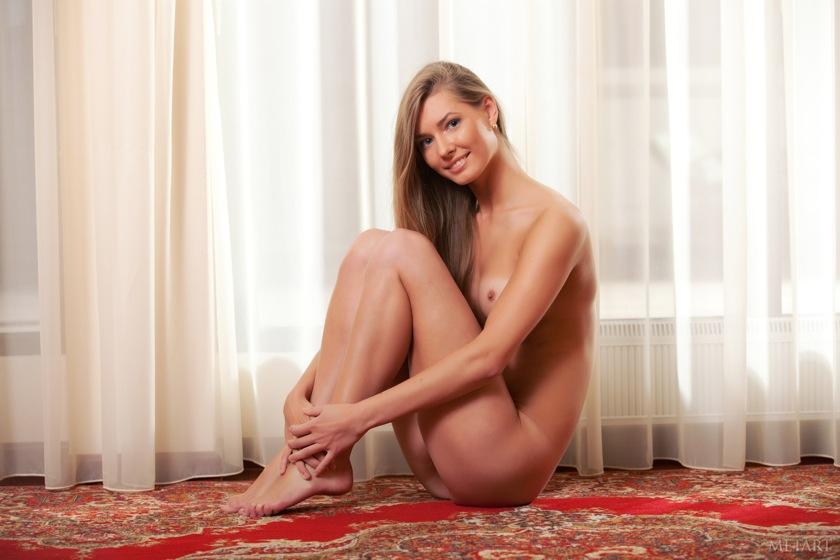 Симпатичная девушка позирует на ковре - фото