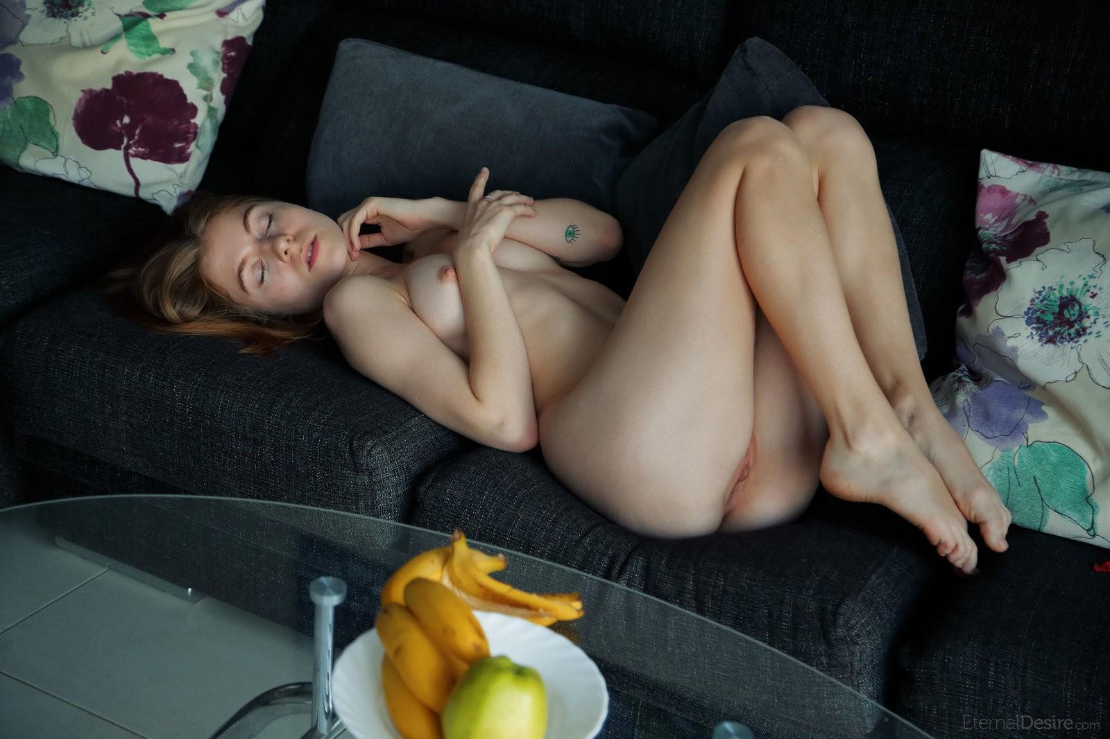 Голая милашка ласкает промежность на диване - фото