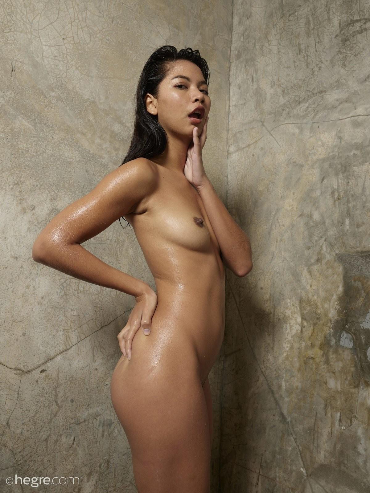 Голая молодая азиатка обливается водой - фото