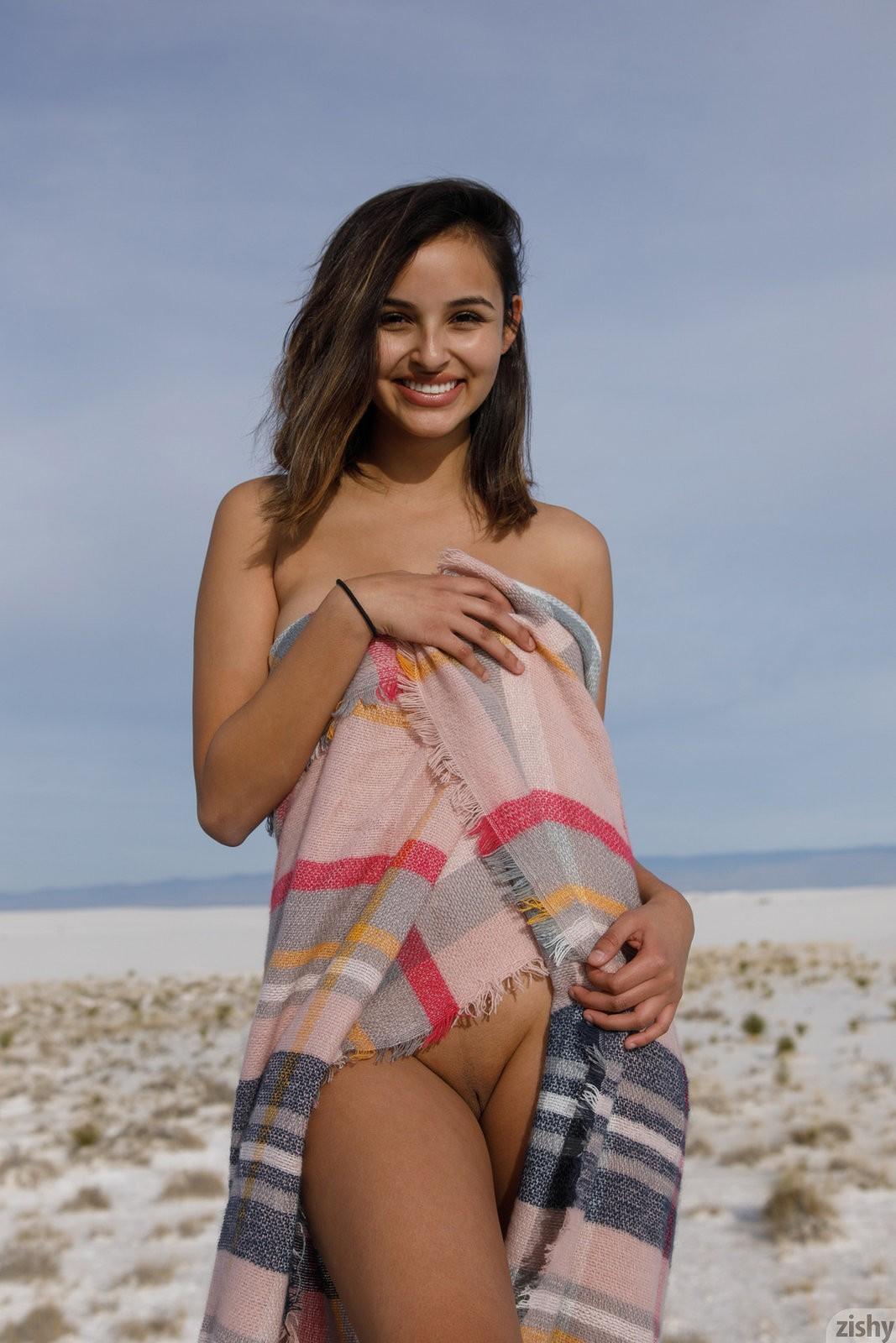 Девушка с сочной жопой позирует на песке - фото