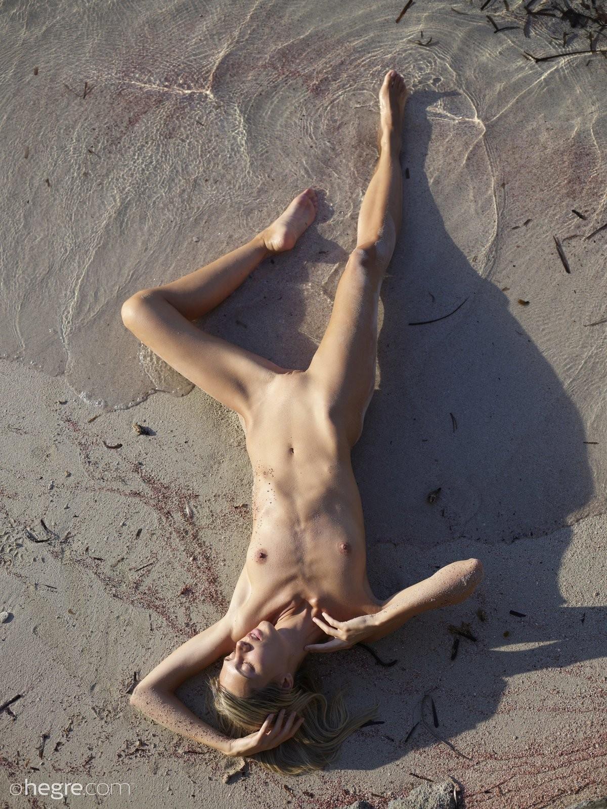 Тощая девушка в песке на пляже - фото