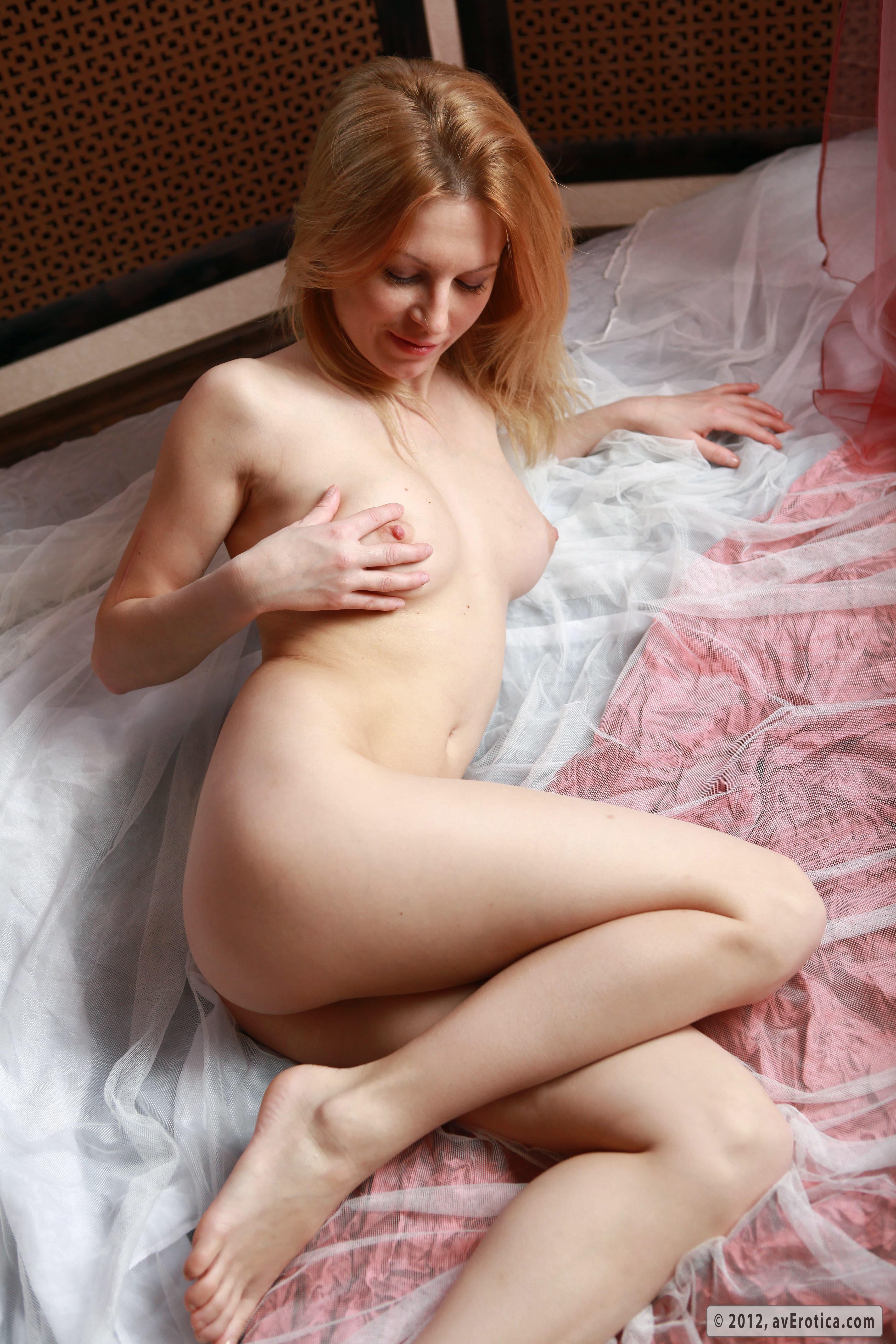 Голая блондинка с упругой жопой на кровати - фото