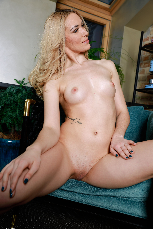 Белобрысая голая девушка в кресле - фото