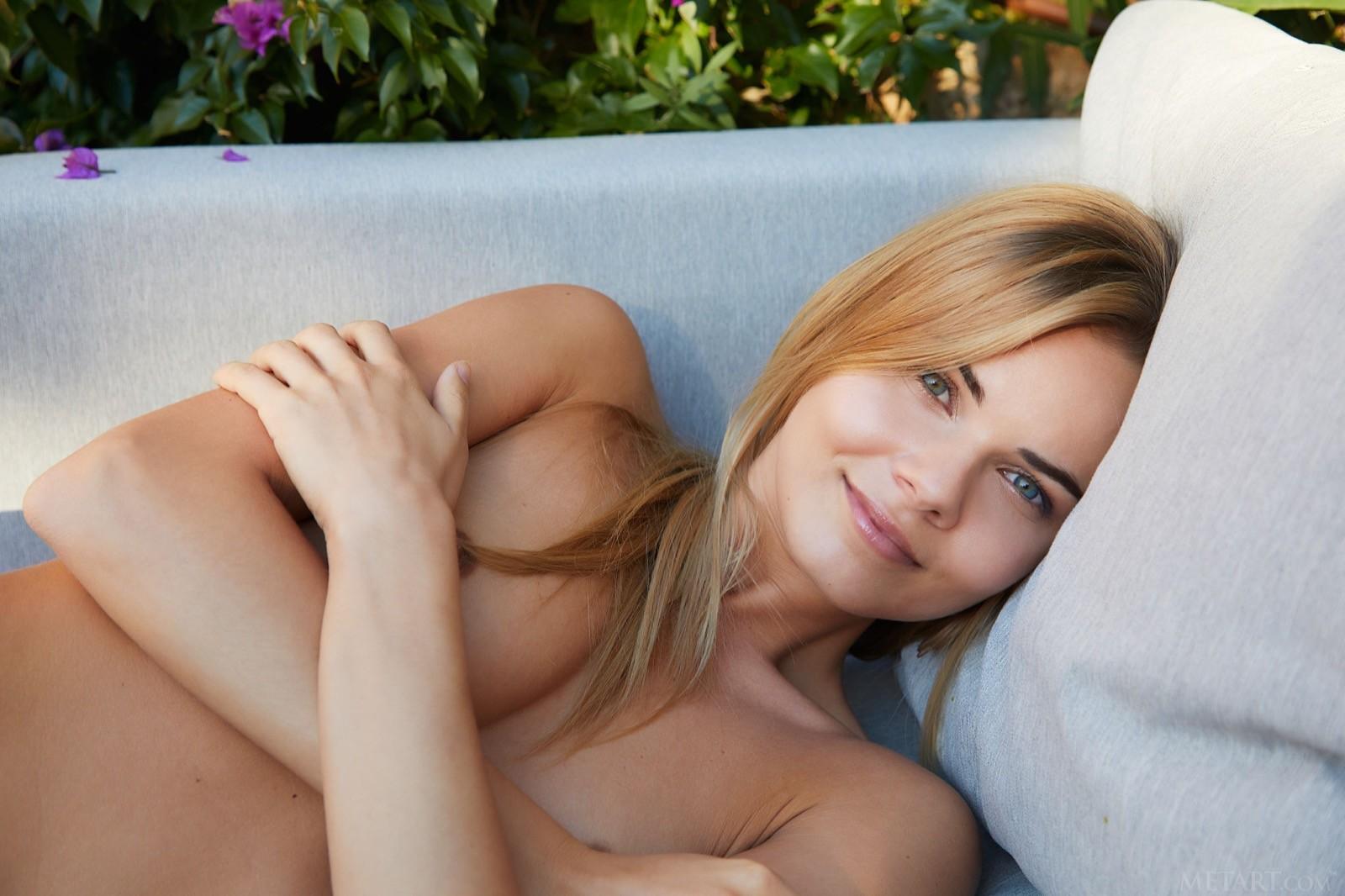 Голая милашка позирует на диванчике - фото