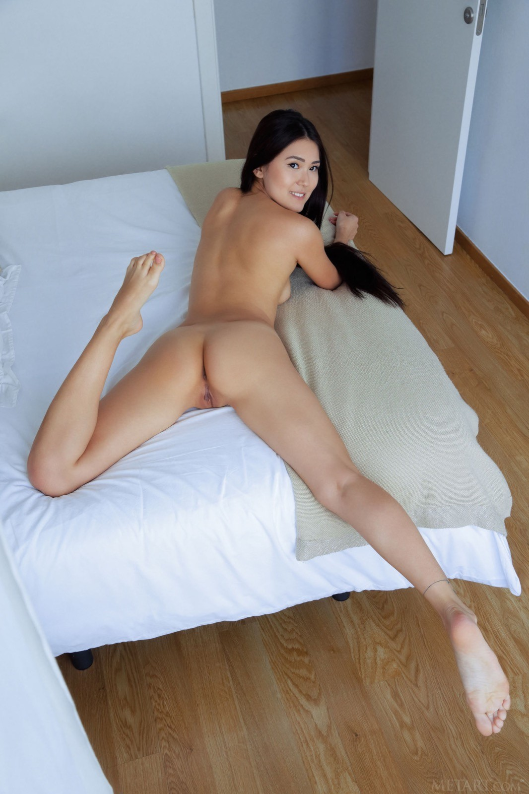 Голая кореянка лежит на кровати - фото