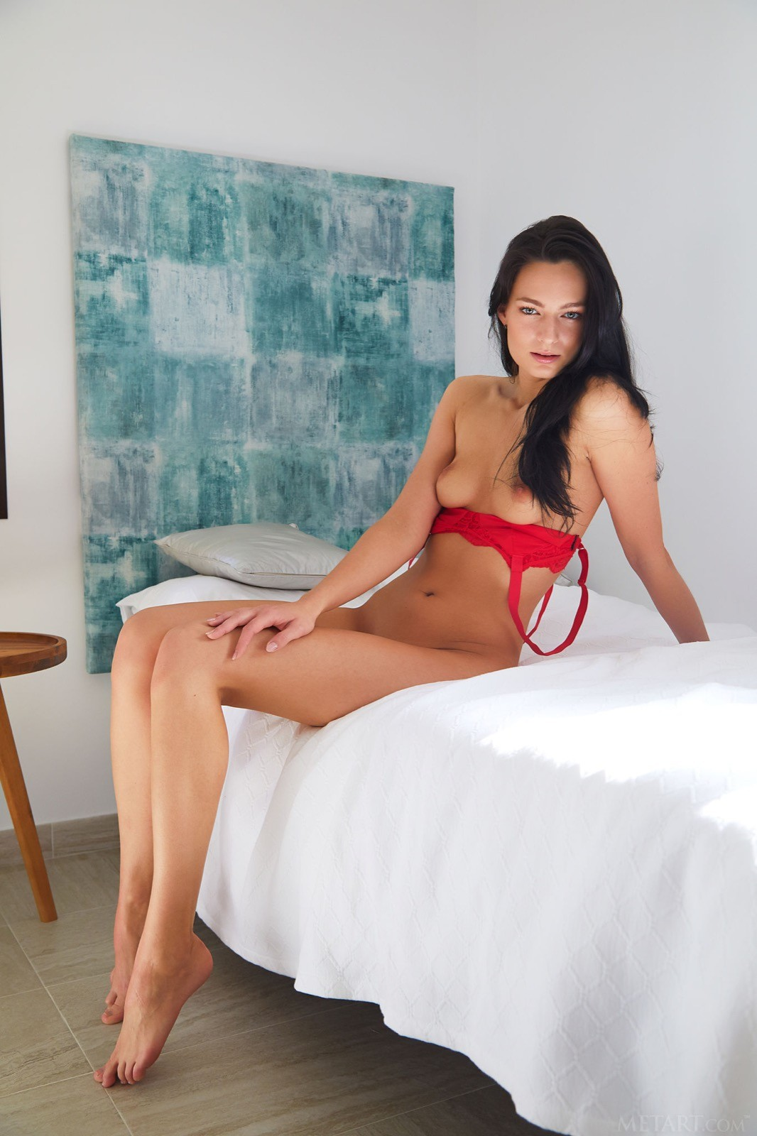 Брюнетка в красном белье на кровати - фото