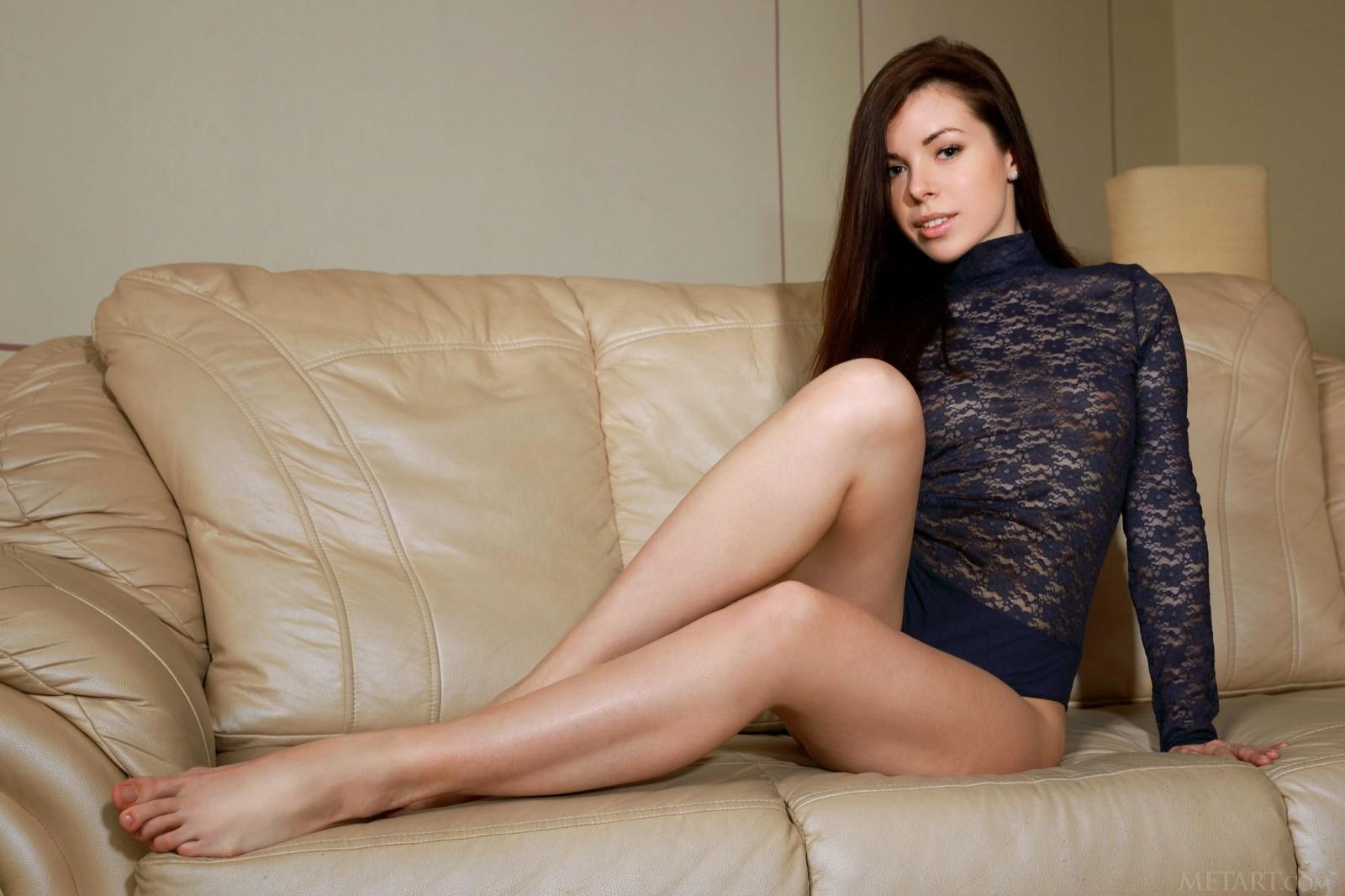 Девушка без трусов на кожаном диване - фото