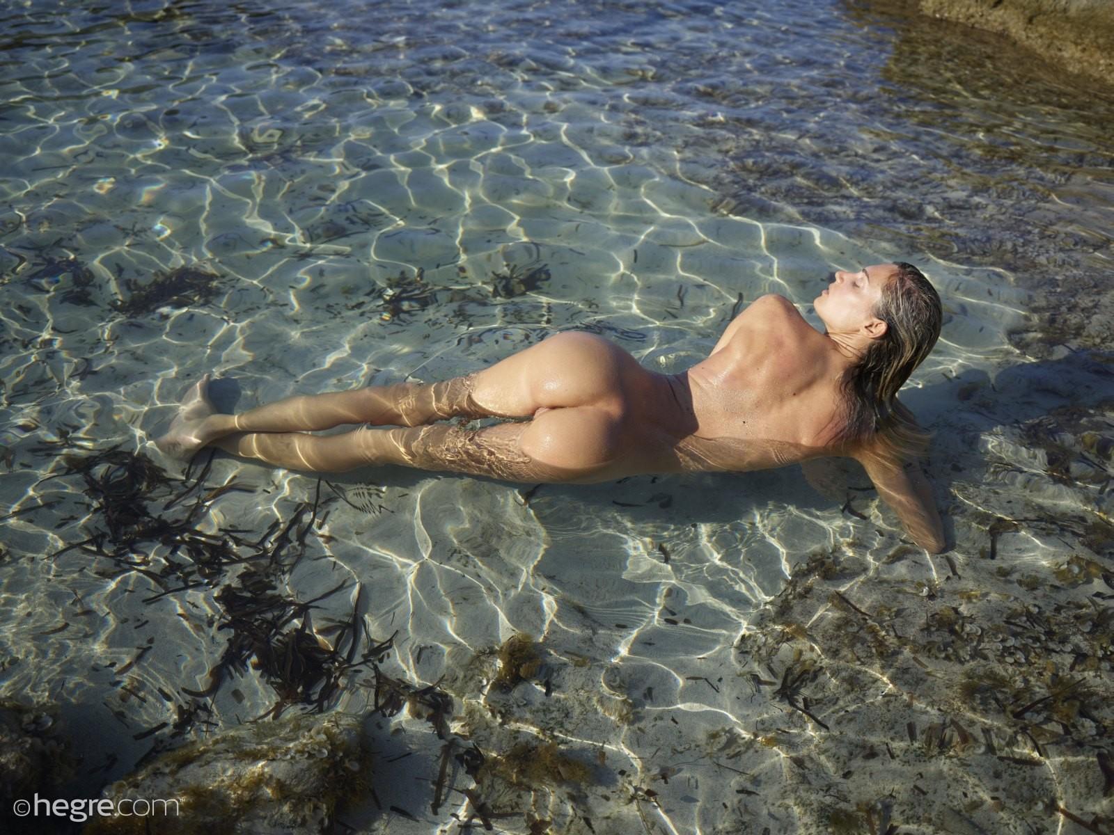 Тощая блондинка голой купается на пляже - фото