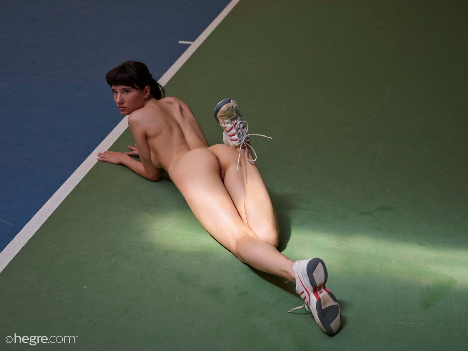 Голая спортсменка в кроссовках лежит на полу - фото