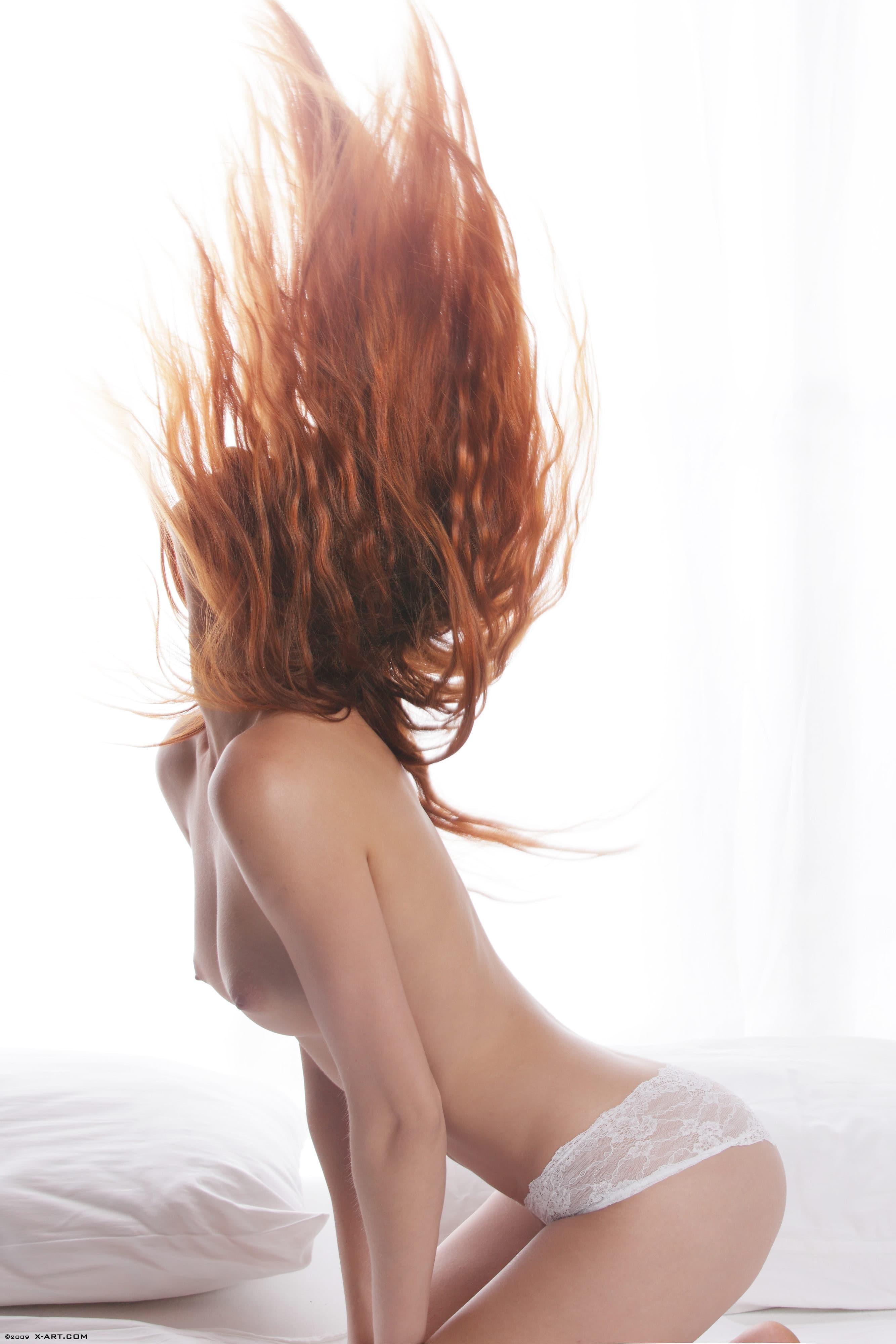 Рыжая красотка сняла трусики на кровати - фото