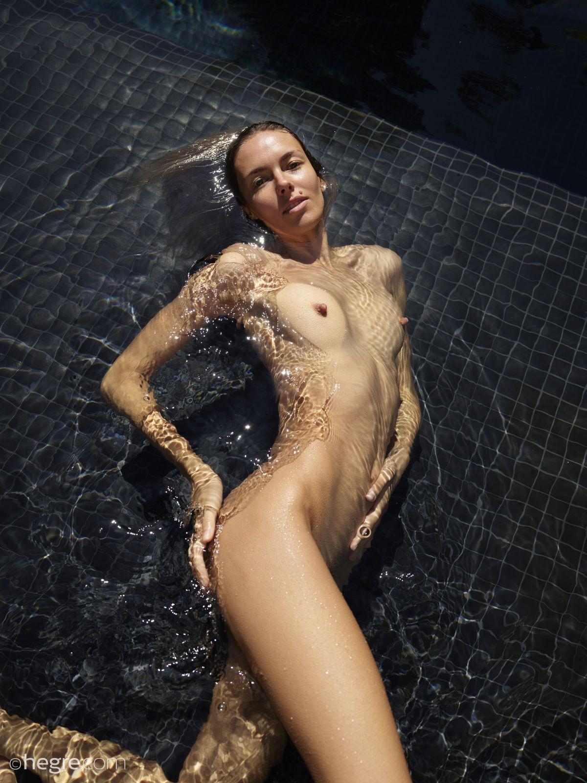 Голая девица плавает в бассейне - фото