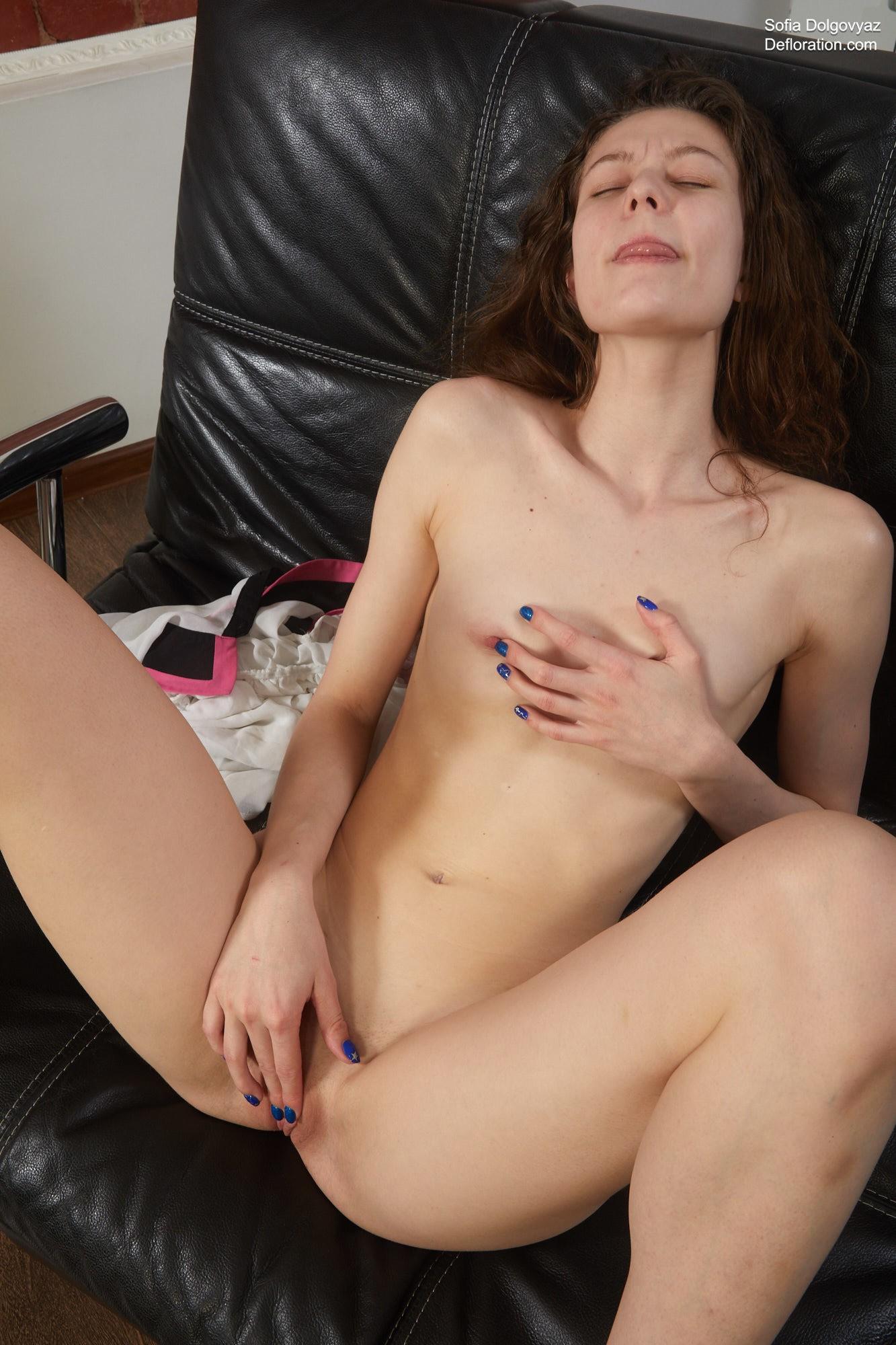 Раздвинув ноги мастурбирует на кожаном диване - фото