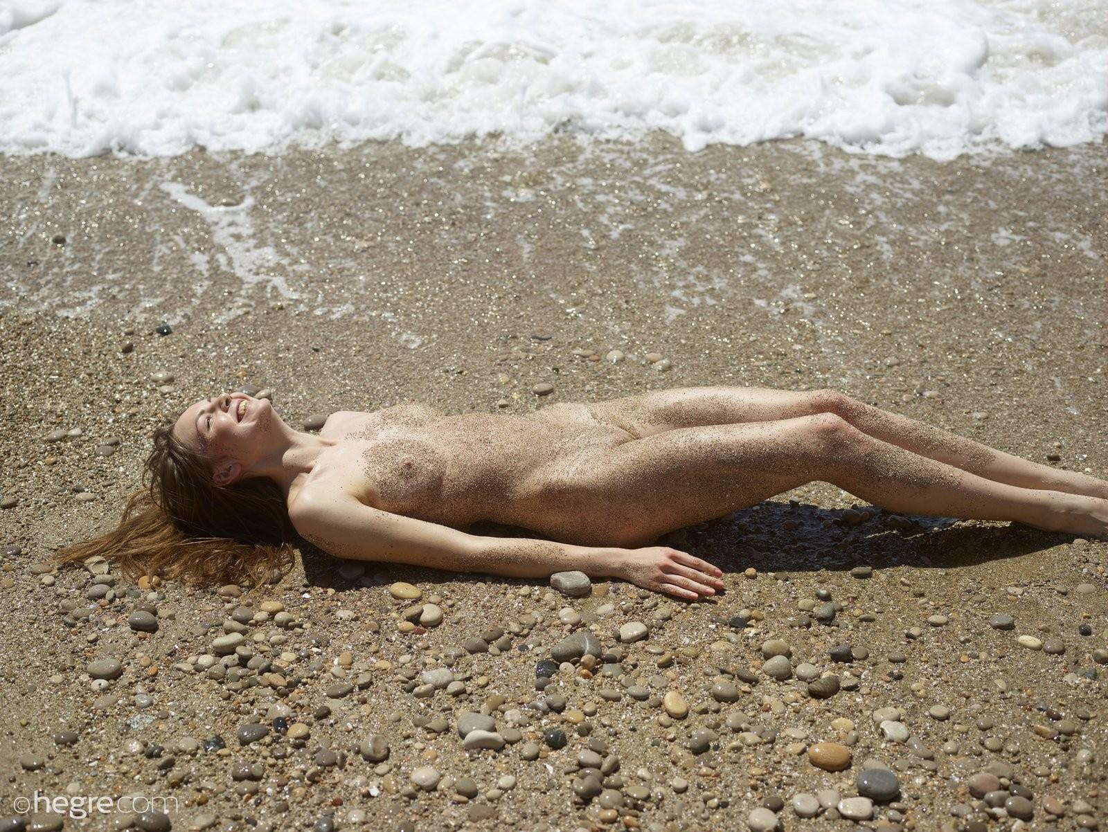 Голая нудистка в песке на пляже - фото