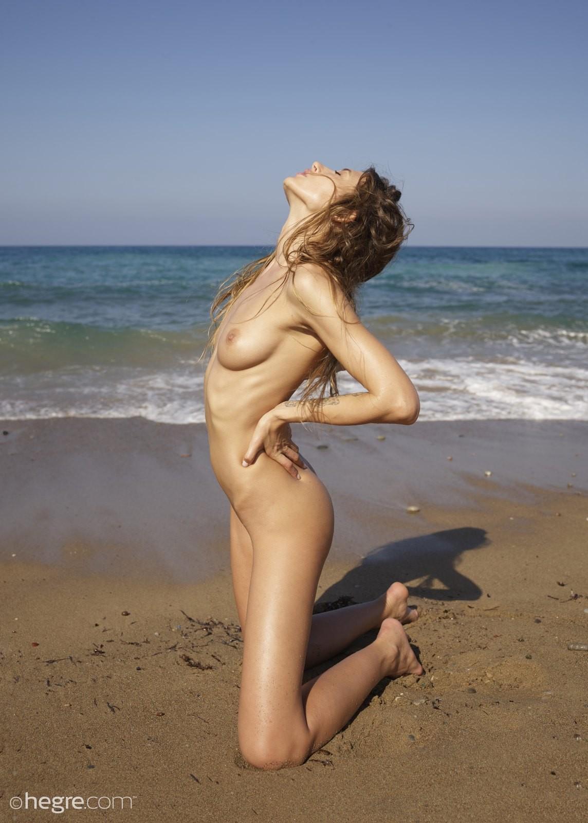 Голая девка позирует на песке у моря - фото
