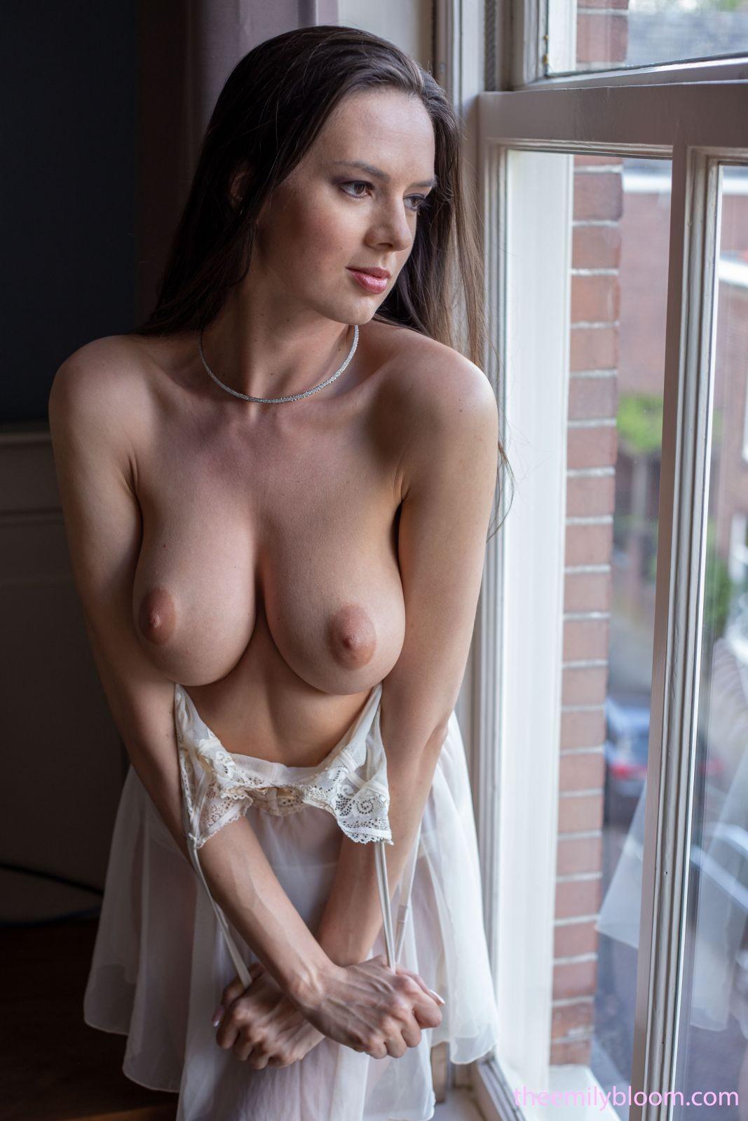 Грудастая мечтательница голая у окошка - фото