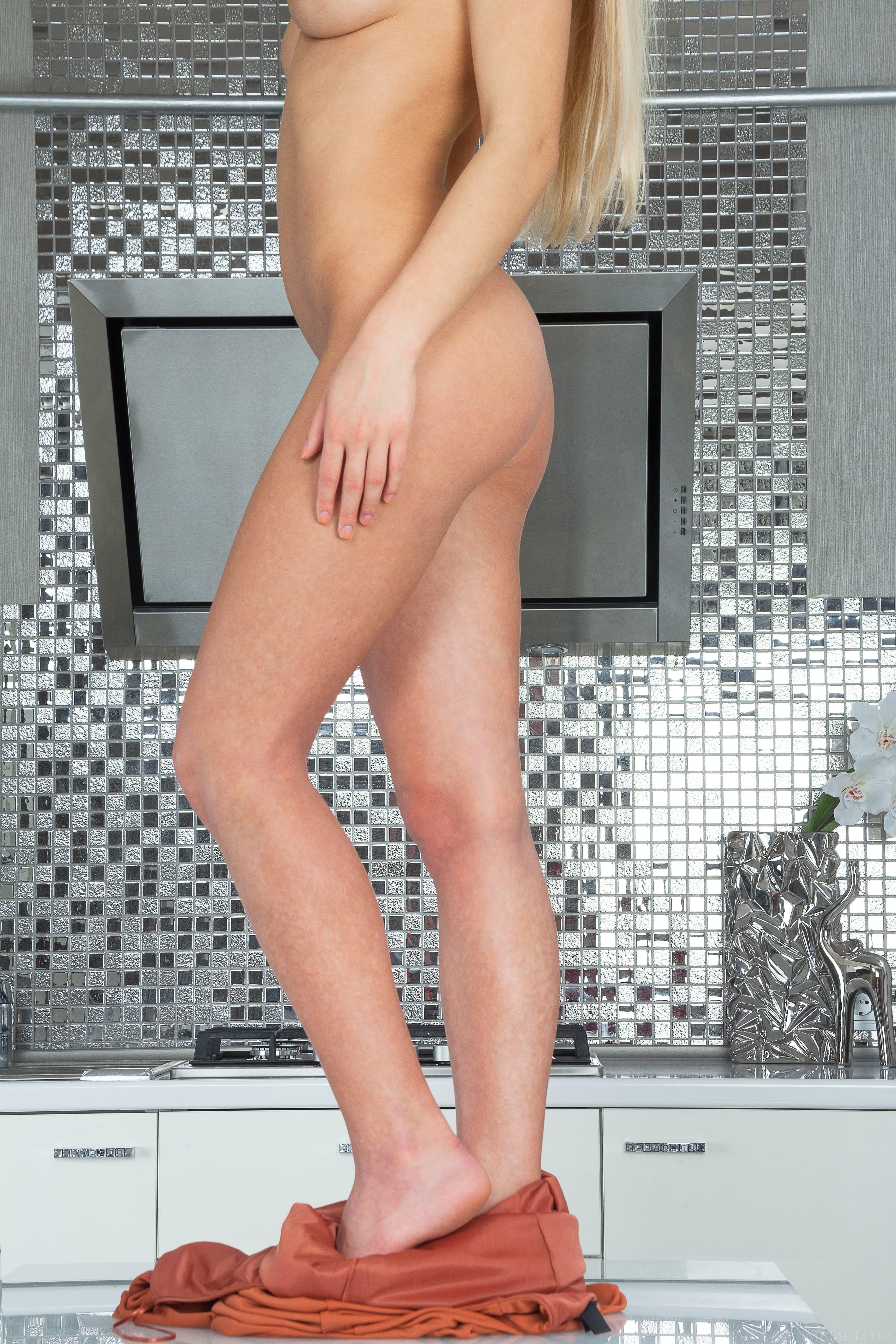 Голая блондинка забралась на кухонный стол - фото