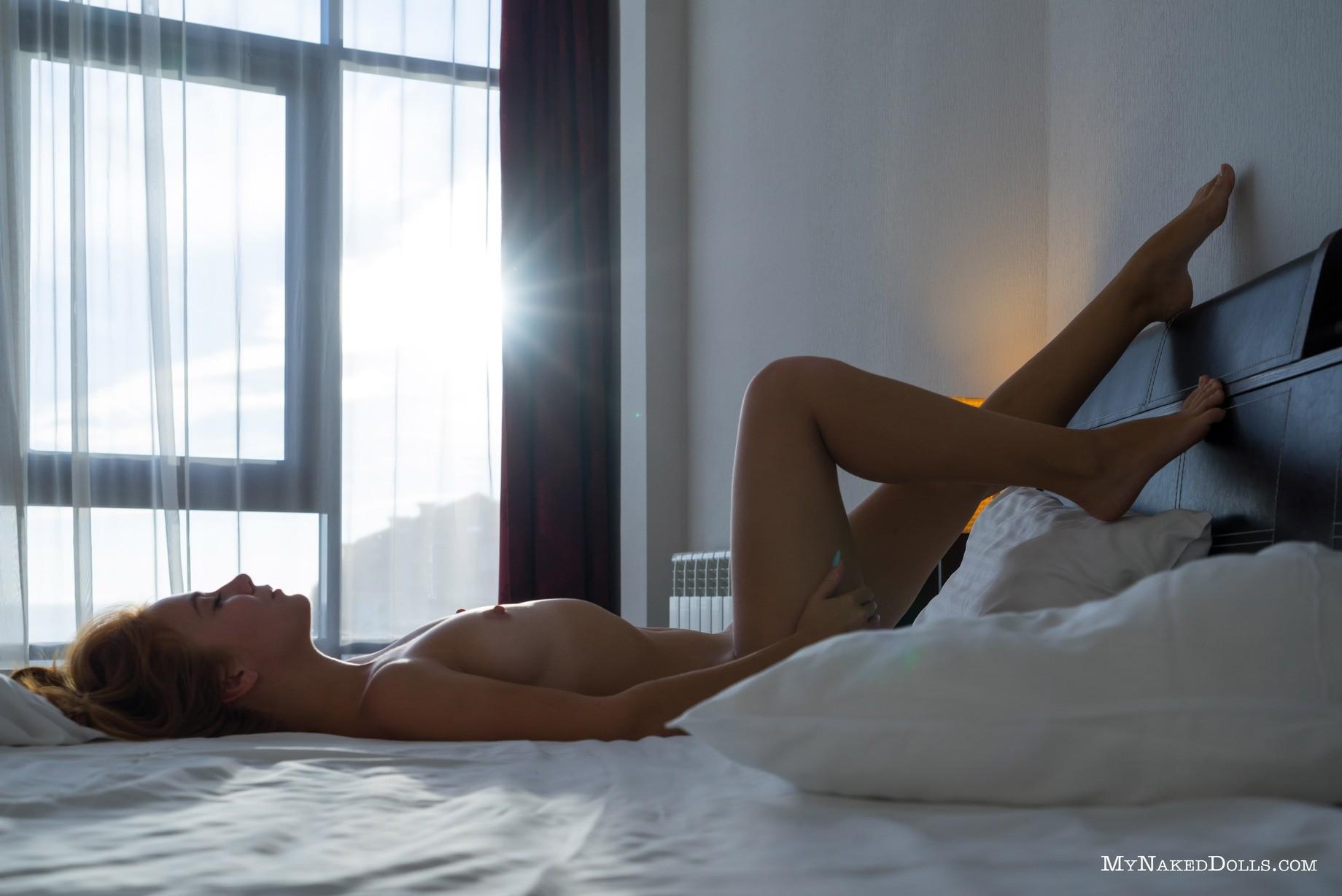 Голая рыжая жена на кровати в номере отеля - фото
