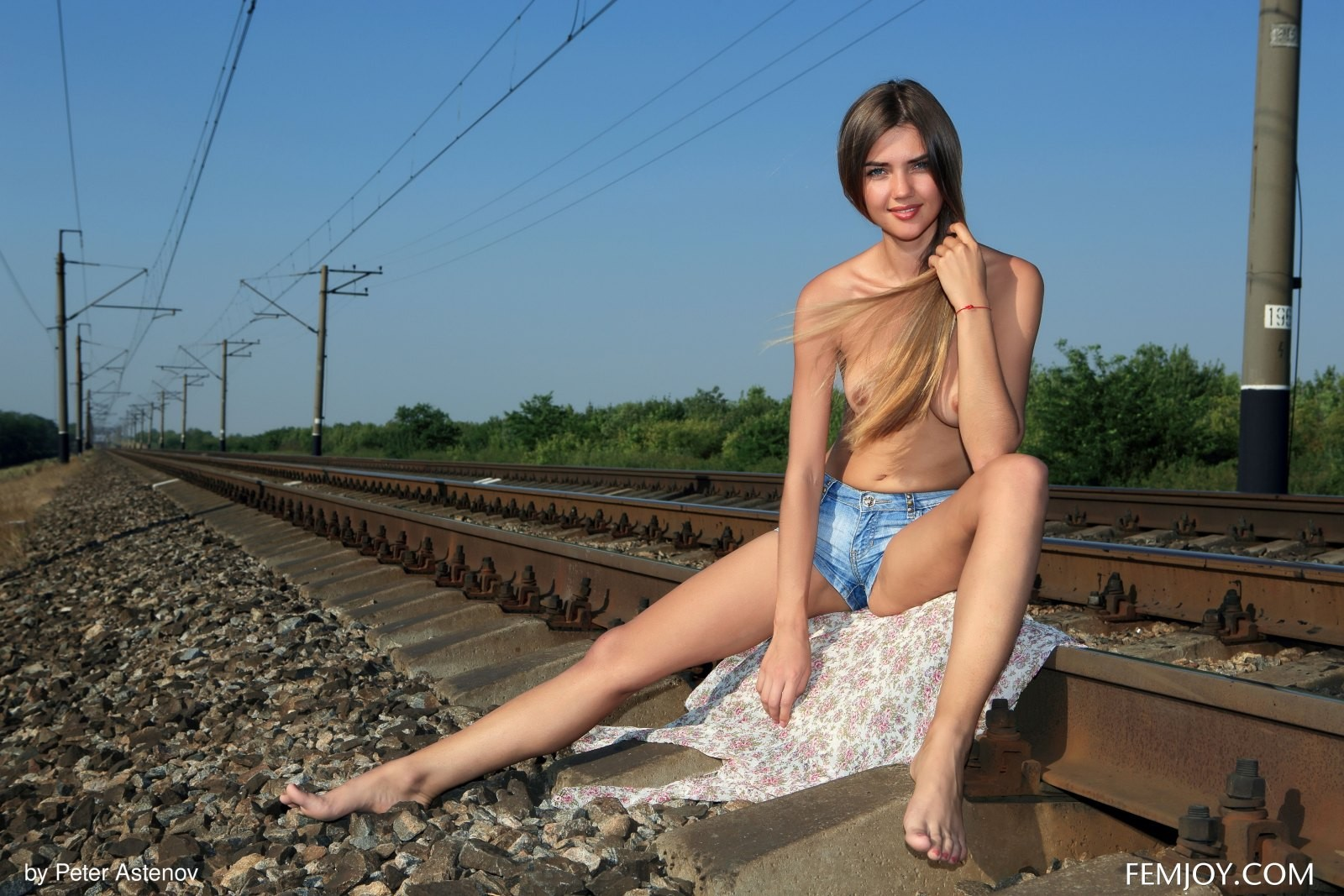 Девка в шортах без лифчика на рельсах - фото