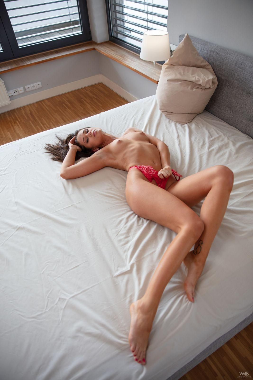 Худая милашка в боди на большой кровати - фото
